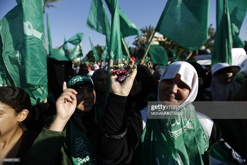 Palestinians wave Hamas flags as they celebrate in Gaza City on August 27, 2014, during a rally following a deal hailed by Israel and the Islamist movement as 'victory' in the 50-day war. The agreement, effective from 1600 GMT on August 26, saw the warring sides agree to a 'permanent' ceasefire which Israel said would not be limited by time, in a move hailed by Washington, the United Nations and top world diplomats.