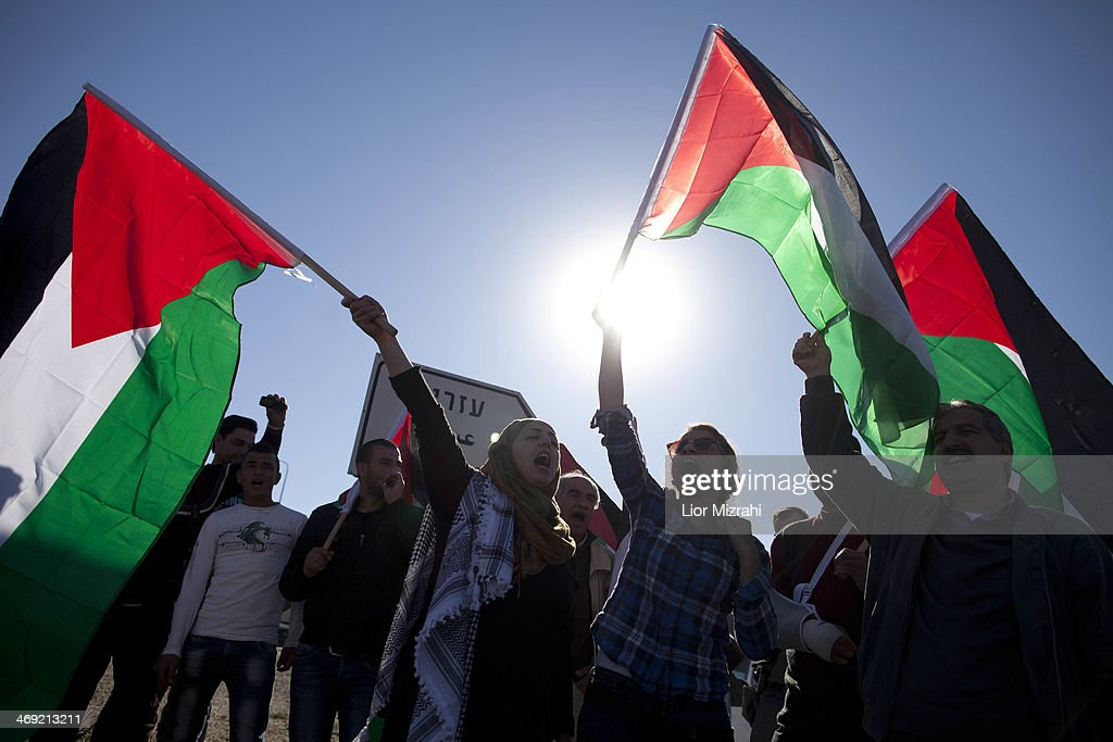 Palestinians wave national flags during a protest against the expansion of the Maaleh Adumim settlement February 13, 2014 at Azarya , West Bank. Israeli rightists and members of Israeli Prime Minister Benjamin Netanyahu's cabinet marched to the contested West Bank area, to protest at Netanyahu's decision to block construction there.