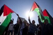 Palestinians wave national flags during a protest against the expansion of the Maaleh Adumim settlement February 13 2014 at Azarya West Bank Israeli...