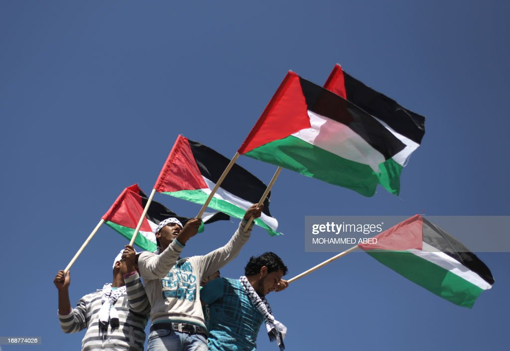 Palestinians wave their flag as they attend the 65th Nakba day or 'Day of Catastrophe' rally in Gaza City, on May 15, 2013. Palestinians and Arab Israelis are marking what to them is the Nakba -- Arabic for 'catastrophe' -- of the creation of the Jewish state and exodus of 760,000 of them from their homes in 1948.