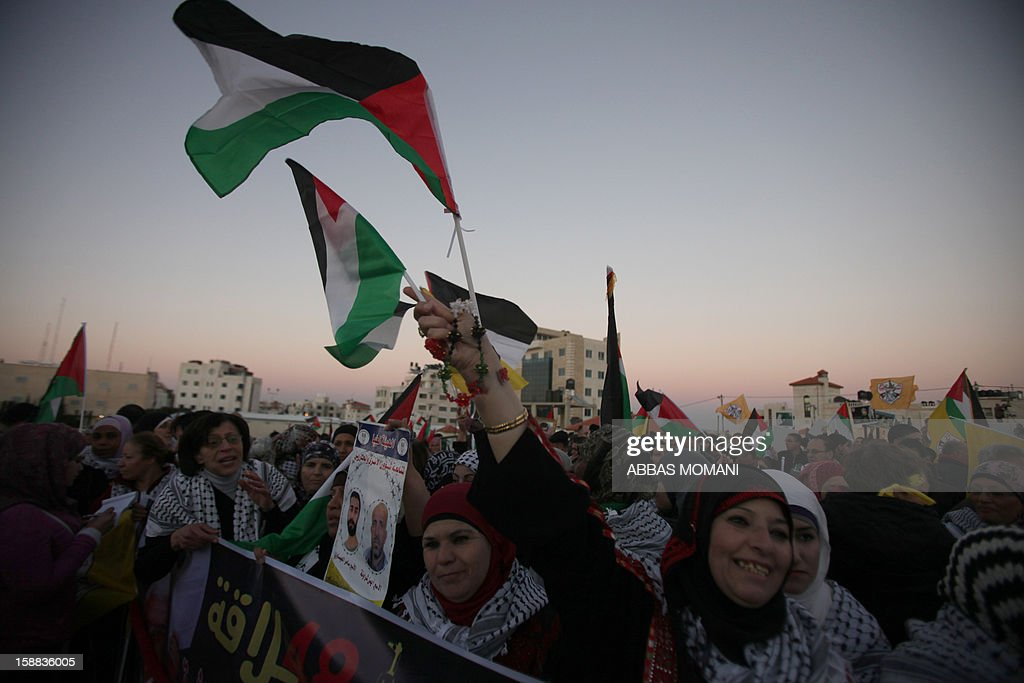 Palestinians wave their flag during a rally on the eve of the 48th anniversary of the formation on the Fatah movement, on December 31, 2012, in the West Bank city of Ramallah. The Fatah anniversary commemorates the first operation against Israel claimed by its armed wing then known as Al-Assifa (The Thunderstorm in Arabic) on January 1, 1965. AFP PHOTO/ABBAS MOMANI