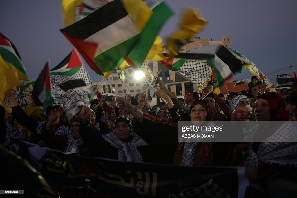 Palestinians wave their flag during a rally on the eve of the 48th anniversary of the formation on the Fatah movement, on December 31, 2012, in the West Bank city of Ramallah. The Fatah anniversary commemorates the first operation against Israel claimed by its armed wing then known as Al-Assifa (The Thunderstorm in Arabic) on January 1, 1965.