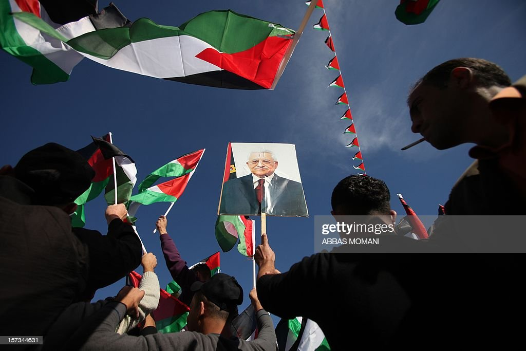Palestinians wave their national flag and a picture of Palestinian president Mahmud Abbas while they celebrate the upgraded United Nations status for the Palestinians in the West Bank city of Ramallah on December 2, 2012. Abbas said 'Palestine has accomplished a historic achievement at the UN,' three days after the United Nations General Assembly granted the Palestinians non-member state observer status in a 138-9 vote. AFP PHOTO / ABBAS MOMANI