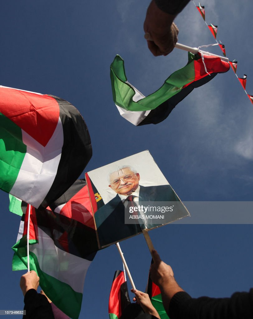 Palestinians wave their national flag and a picture of Palestinian president Mahmud Abbas as they celebrate the upgraded United Nations status for the Palestinians in the West Bank city of Ramallah on December 2, 2012. Abbas said in a speech he delivered to cheering crowds that 'Palestine has accomplished a historic achievement at the UN,' three days after the United Nations General Assembly granted the Palestinians non-member state observer status in a 138-9 vote.