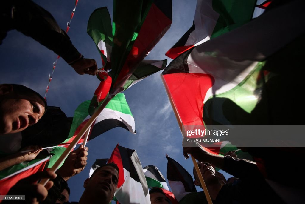 Palestinians wave their national flag as they celebrate the upgraded United Nations status for the Palestinians in the West Bank city of Ramallah on December 2, 2012. Palestinian president Mahmud Abbas said is speech on his visit to Ramallah that 'Palestine has accomplished a historic achievement at the UN,' three days after the United Nations General Assembly granted the Palestinians non-member state observer status in a 138-9 vote. AFP PHOTO / ABBAS MOMANI