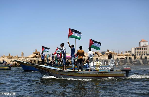 Palestinians wave their national flag as they ride boats during a rally in support of activists aboard a ProGaza flotilla made up of four boats aimed...