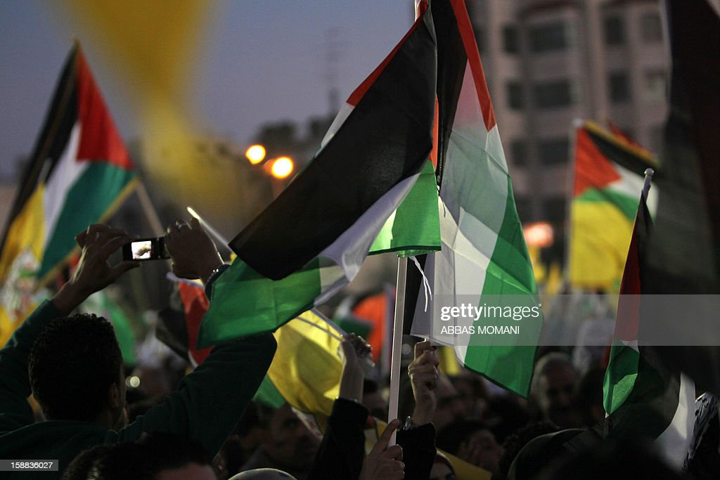 Palestinians wave their national flag during a rally on the eve of the 48th anniversary of the formation on the Fatah movement, on December 31, 2012, in the West Bank city of Ramallah. The Fatah anniversary commemorates the first operation against Israel claimed by its armed wing then known as Al-Assifa (The Thunderstorm in Arabic) on January 1, 1965.