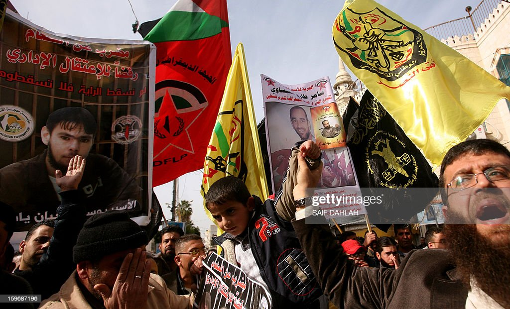 Palestinians waves Fatah party flags and hold pictures of relatives and individuals detained in Israeli prisons during a demonstration in the West Bank city of Jenin on January 18, 2013, in support with Palestinians on hunger strike in Israeli jails and against administrative detention.