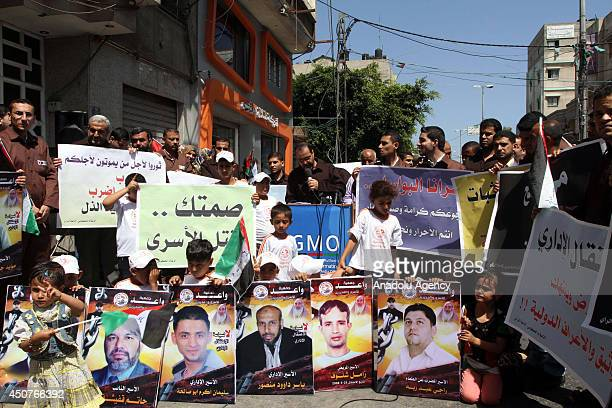 Palestinians wear prisoners suits take part in a protest in support of Palestinians prisoners detained in Israeli jails and who have been on hunger...