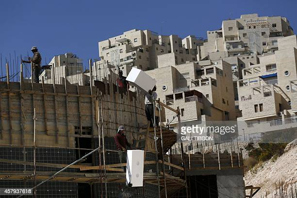 Palestinians work at a construction site of a new housing project in the annexed Arab east Jerusalem neighborhood of Jabal Abu Ghneim where the...