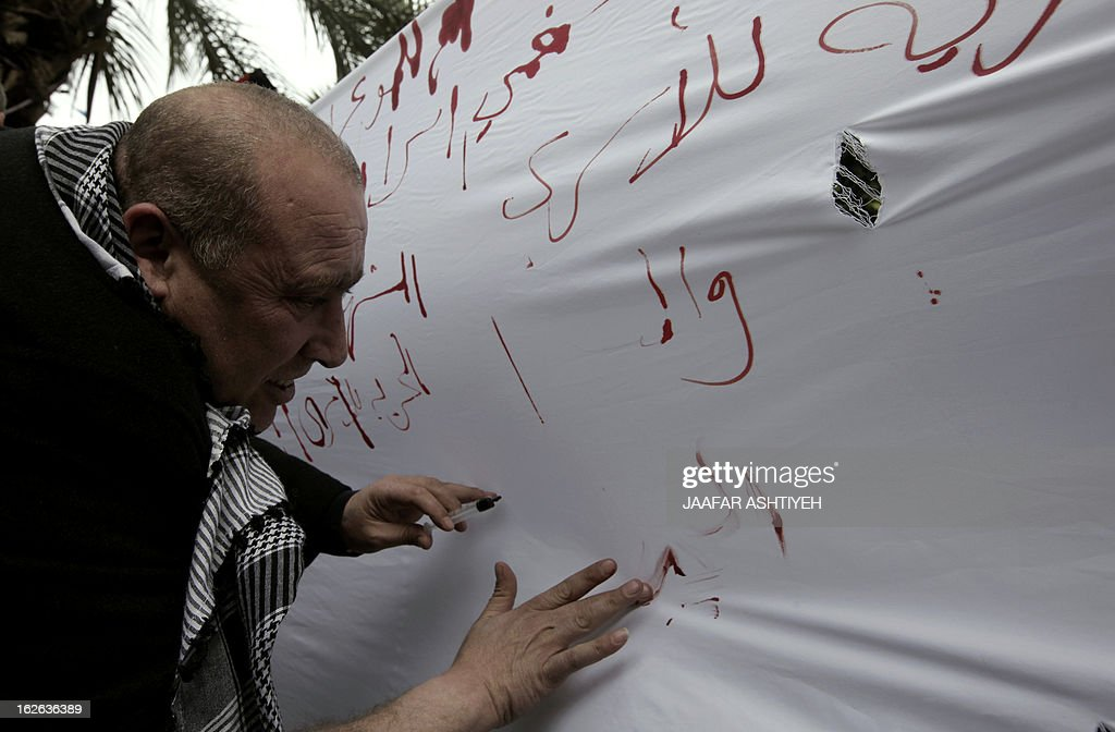 Palestinians write letters in blood on a banner during a demonstration in support of the Palestinian prisoners in Israeli jails, in the city of Nablus, in the occupied West Bank, on February 25, 2013. Protests in support of Palestinian prisoners on hunger strike in Israeli prisons have been building and gained new momentum with the sudden death in his cell on February 23, of 30-year-old Arafat Jaradat, a former militant of Palestinian president Mahmud Abbas's Fatah movement.