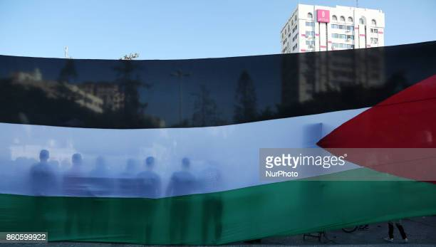 Palestinians youth poses in front of his national flag during celebrations in Gaza City after rival Palestinian factions Hamas and Fatah reached an...