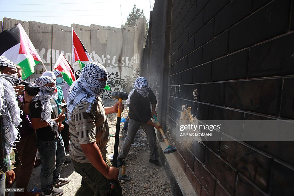 Palestinians youth use sledge hammers to knock holes through part of a wall connected to Israel's controversial separation barrier in the Abu Dis neighrbood, bordering Jerusalem on July 9, 2013. Israel says the barrier is needed to prevent attacks but Palestinians, who refer to it as an 'Apartheid Wall,' say it cuts them off from occupied land that should be part of their future state. The International Court of Justice (ICJ) issued a non-binding resolution in 2004 calling for those parts of the barrier inside the West Bank to be torn down and for further construction in the territory to cease. Israel has ignored the ICJ ruling. AFP PHOTO/ABBAS MOMANI