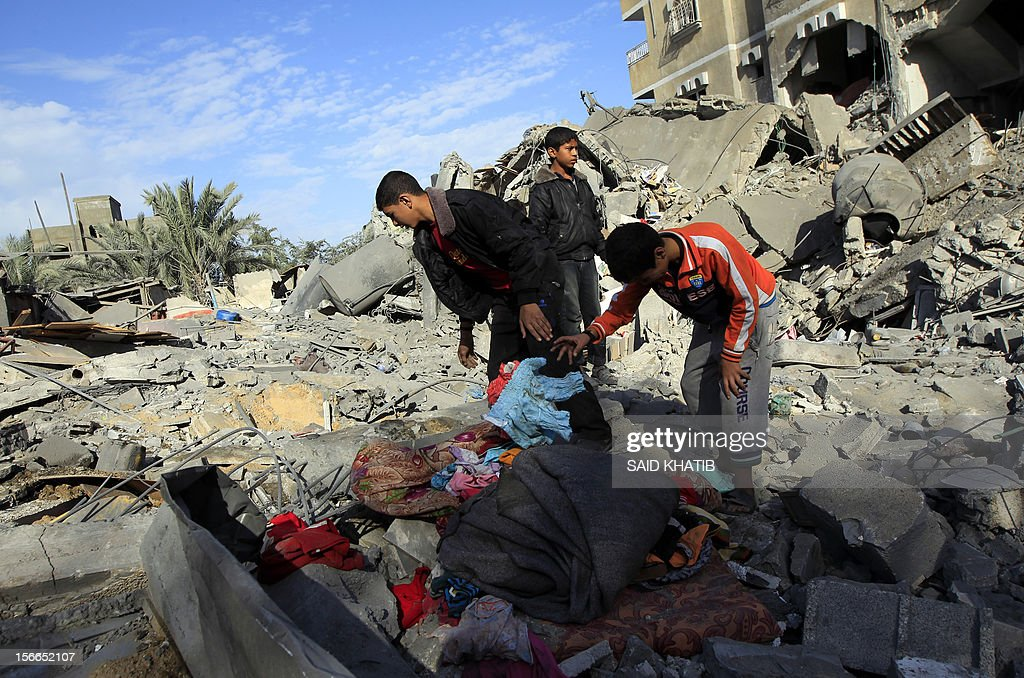 Palestinians youths search through the rubble of destroyed buildings following Israeli air strikes on the southern Gaza Strip town of Rafah on November 18, 2012. Israeli war planes hit a Gaza City media centre and homes in northern Gaza in the early morning, as the death toll mounted, despite suggestions from Egypt's President Mohamed Morsi that there could be a 'ceasefire soon.'