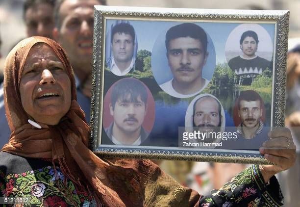 Palistinian woman holds photos of prisoners during a demonstration in support of the more than 2000 prisoners on hunger strike in Israeli jails on...