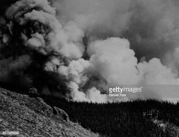 A pall of smoke lies over the forested slopes of Mt Evans about 35 miles west of Denver as roaring flames chew through acres if timber Fire fighters...
