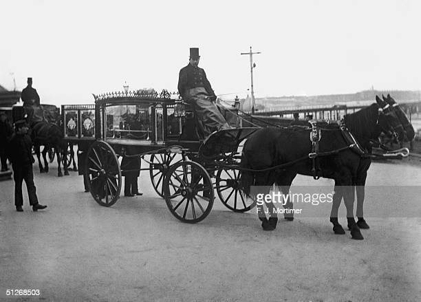 Pallbearers attend a glass sided funeral carriage in Portsmouth circa 1900