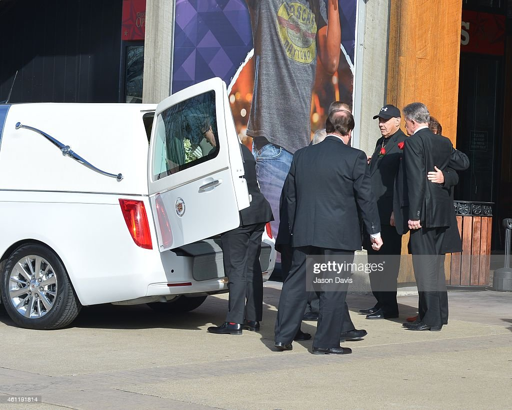 Pallbearers Bill Anderson, Jim Ed Brown, John Conlee, Vince Gill, Brad Paisley, Mel Tillis, Larry Tucker, Bobby Tomberlin and Robbie Wittkowski comfort each other after loading the casket containing Little Jimmy Dickens into a white hearse during his Public Celebration of Life at The Grand Ole Opry on January 8, 2015 in Nashville, Tennessee.
