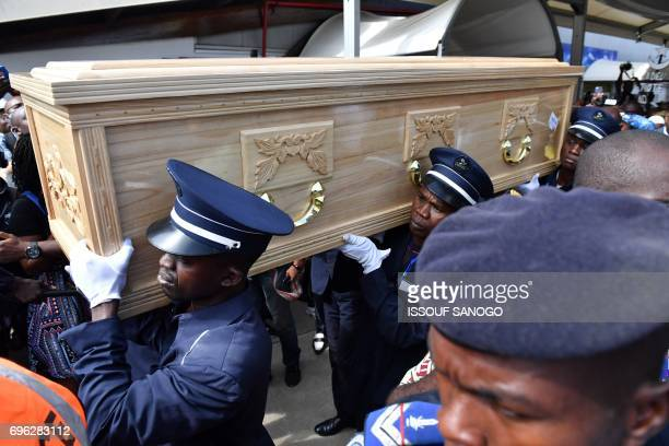 Pallbearers carry the casket of the late Ivory Coast midfielder Cheick Tiote on June 15 2017 upon its arrival from China at Abidjan's airport prior...