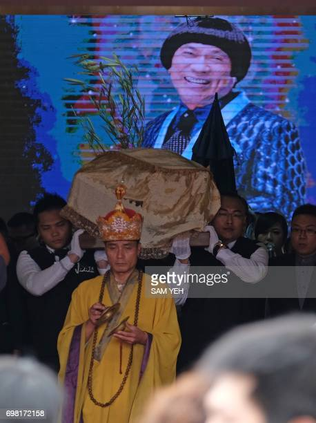 Pallbearers carry the coffin of late Taiwanese celebrity Chu Keliang from a local funeral parlor in New Taipei City on June 20 2017 Lion dancers and...