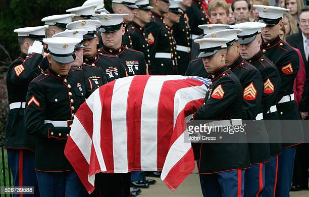 Pallbearers carry the flag drapped coffin with the remains of Lance Corporal Nicholas Larson from Saint John the Baptist Catholic Church in Winfield...
