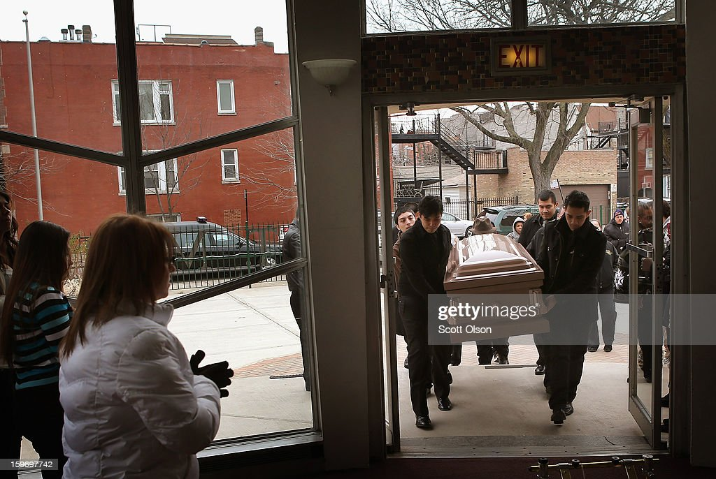 Pallbearers carry the remains of Rey Dorantes, 14, into St. Mark Church for a funeral mass on January 18, 2013 in Chicago, Illinois. Dorantes died after being shot six times while he was sitting on the front porch of his home while talking on the phone on January 11. Dorantes' murder was the 21st homicide recorded in Chicago for 2013, a city which saw more than 500 homicides in 2012.