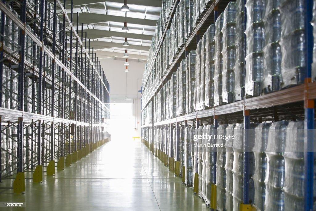 Pallets of water bottles on warehouse shelves