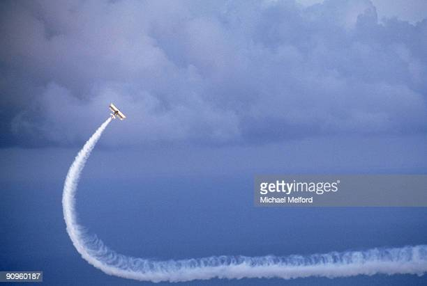 A biplane makes a white curved pattern in the sky.