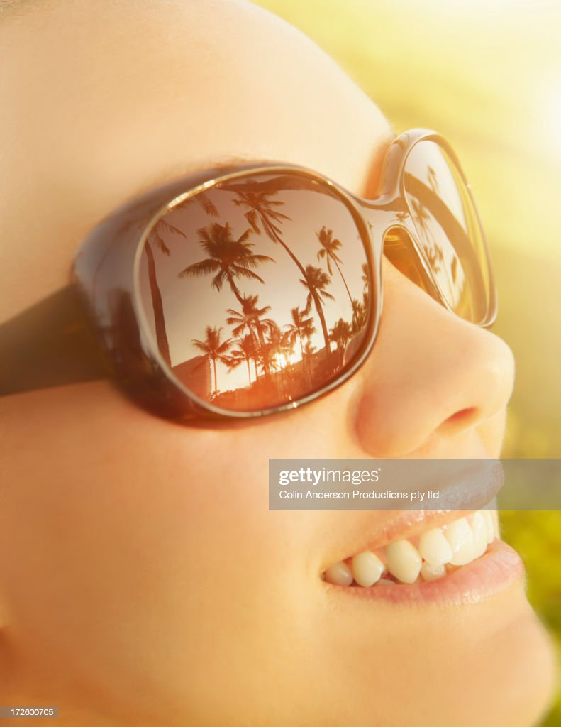 Palm trees reflected in Pacific Islander woman's sunglasses : Stock Photo