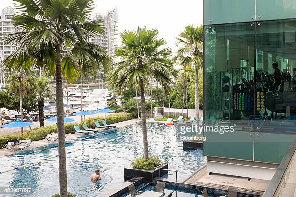 Palm trees stand at a swimming pool's edge at the One Degree 15 Marina Club venue for the Singapore Yacht Show in Singapore on Thursday April 10 2014...