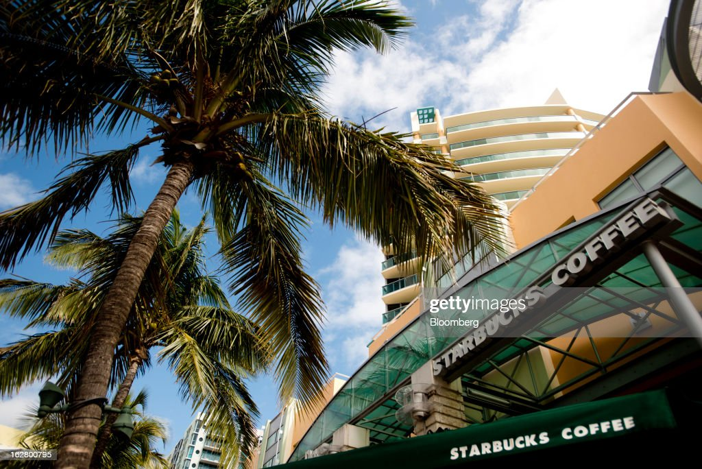 Palm trees tower over a Starbucks Corp. coffee shop in the South Beach neighborhood of Miami Beach, Florida, U.S., on Wednesday, Feb. 20, 2013. U.S. exports in the travel and tourism sector reached $168.1 billion in 2012, up 10.1 percent from the year-ago level of $152.7 billion, according to data released Feb. 22 by the Commerce Department's International Trade Administration. Photographer: Ty Wright/Bloomberg via Getty Images