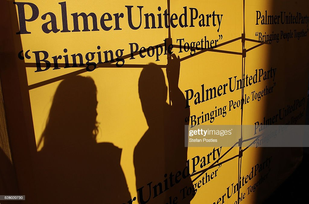 Palmer United staff secure a sign during a press conference at Parliament House on May 4, 2016 in Canberra, Australia. The Turnbull Goverment's first budget has delivered tax cuts for small and medium businesses, income tax cuts people earning over $80,000 a year,new measures to help young Australians into jobs and cutbacks to superannuation concessions for the wealthy.