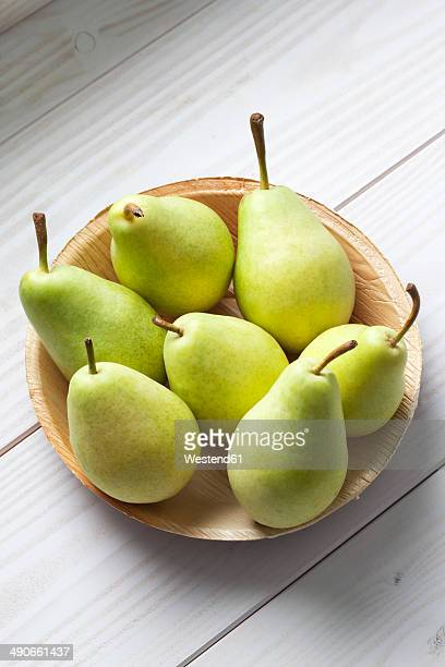 Palmleaf plate of pears (Pyrus) on white wooden table