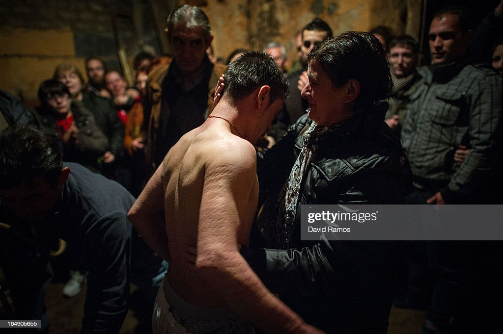 Paloma Martin comforts her son Cesar Higuero Martin, aged 25, after he had walked the way of the cross or 'Via Crucis' at the end of the procession of the 'Empalaos' on March 29, 2013 in Valverde de la Vera, Spain. Empalaos make the steps of the 'Via Crucis', marking the Stations of the Cross, during the night of Maundy Thursday while bound by rope to a crucifix as an act of penance and to honour a promise made to the Empalaos Brotherhood and the Christ of Vera Cruz, in the town of Valverde de la Vera. The process of dressing the Empalao in the traditional costume is taken with great care, with the family and dressers paying attention to ensure that no harm is caused to the penitent and that they are aided in their recovery, including being massaged and rubbed with rosemary alcohol. Many Spanish towns and villages retain such rites and religious traditions, many passed down from medieval times, across the Easter weekend.