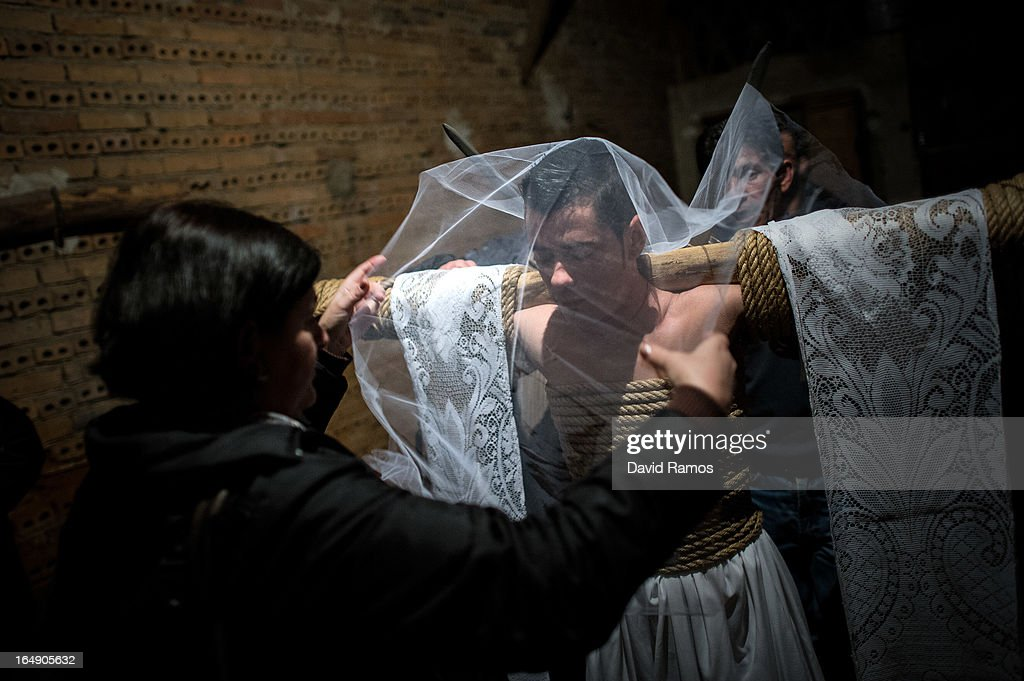 Paloma Martin puts the veil on her son Cesar Higuero Martin, aged 25, before walking the way of the cross or 'Via Crucis' at the end of the procession of the 'Empalaos' on March 29, 2013 in Valverde de la Vera, Spain. Empalaos make the steps of the 'Via Crucis', marking the Stations of the Cross, during the night of Maundy Thursday while bound by rope to a crucifix as an act of penance and to honour a promise made to the Empalaos Brotherhood and the Christ of Vera Cruz, in the town of Valverde de la Vera. The process of dressing the Empalao in the traditional costume is taken with great care, with the family and dressers paying attention to ensure that no harm is caused to the penitent and that they are aided in their recovery, including being massaged and rubbed with rosemary alcohol. Many Spanish towns and villages retain such rites and religious traditions, many passed down from medieval times, across the Easter weekend.