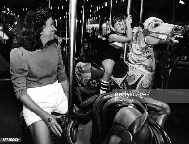 Pam Allen president of the Highlands Ranch Community Association shares a ride on Elitch's carousel with Todd Ognibene age 7 Monday night during a...