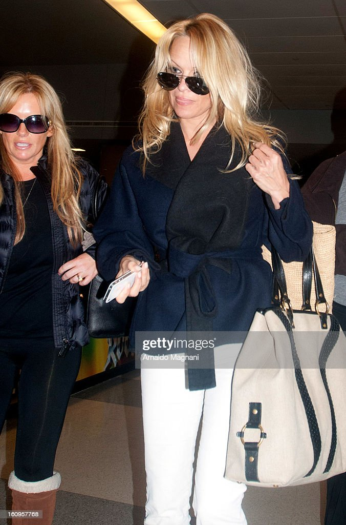 Pamela Anderson (L) arrives at JFK airport on February 07, 2013 in New York City.