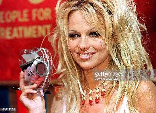 Pamela Anderson holds one of her heartshaped makeup kits during an event to unveil her new 'crueltyfree' cosmetic line named 'Pamela' at Caesar's...