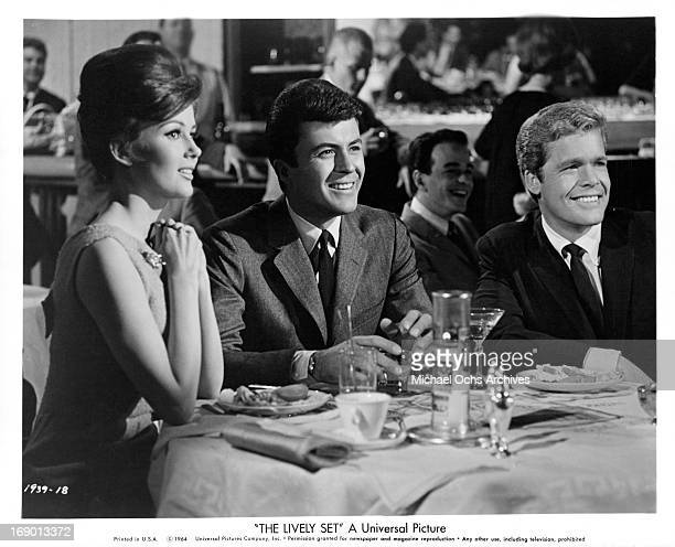 Pamela Tiffin James Darren and Doug McClure sitting at a table enjoying live entertainment in a scene from the film 'The Lively Set' 1964