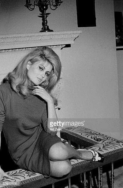 Pamela Tiffin seated on a fireplace bench circa 1970 New York
