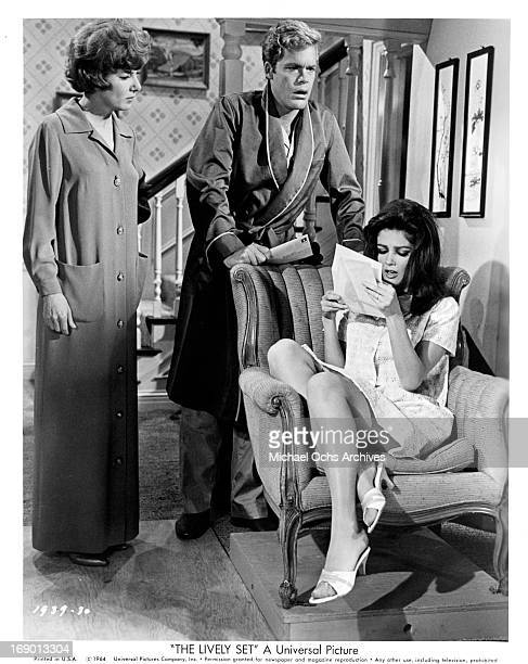 Pamela Tiffin sits in a chair reading a letter as Doug McClure stands over her in a scene from the film 'The Lively Set' 1964