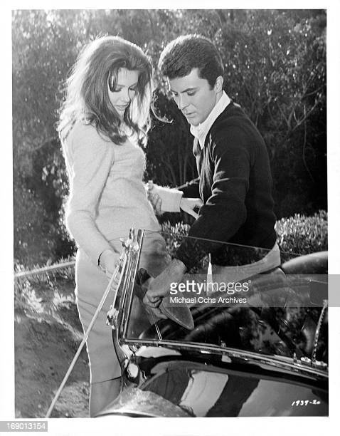 Pamela Tiffin stands on one foot while James Darren looks at the bottom of her shoe in a scene from the film 'The Lively Set' 1964