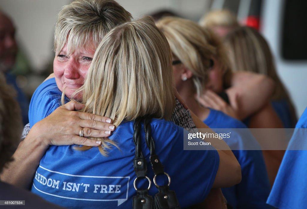 Pamela Toppen (L) gets a hug after the remains of her son Pfc. Aaron Toppen were loaded into a hearse after arriving at Midway Airport on a charter aircraft from Dover Air Force Base on June 21, 2014 in Chicago, Illinois. Toppen, 19, was killed alongside four other American Soldiers and an Afghan soldier in a friendly fire airstrike during a firefight earlier this month in Afghanistan.