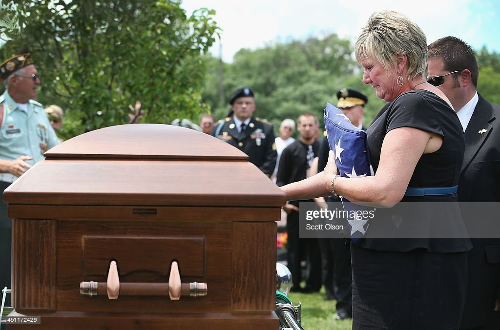 Pamela Toppen says goodbye to her son, U.S. Army Pfc. Aaron Toppen, following a graveside service at St. Johns Cemetery on June 24, 2014 in Mokena, Illinois. Toppen, 19, was killed alongside four other American soldiers and an Afghan soldier in a friendly fire airstrike while they were engaged in a firefight earlier this month in Afghanistan.