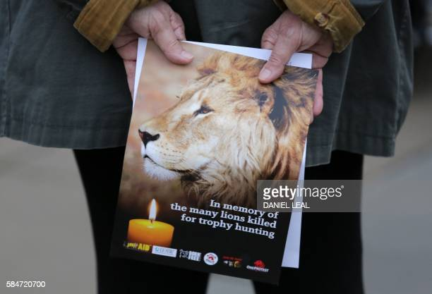 A pamphlet showing an image of Cecil the lion is held at a vigil in central London on July 30 2016 Cecil was killed by American dentist and trophy...