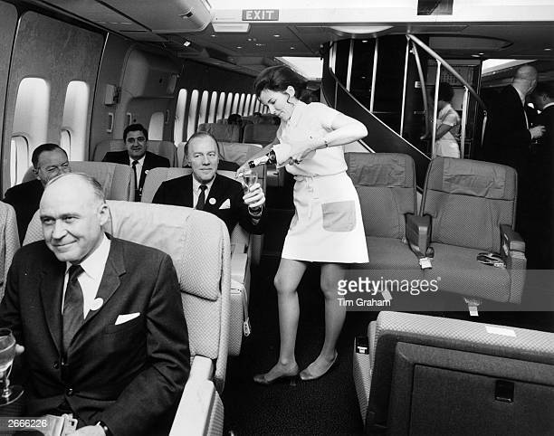 A Pan American airhostess serving champagne in the first class cabin of a Boeing 747 jumbo jet