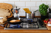 Pan fried salmon fillet and spaghetti on a gas stove in traditional home kitchen. Wood worktop.