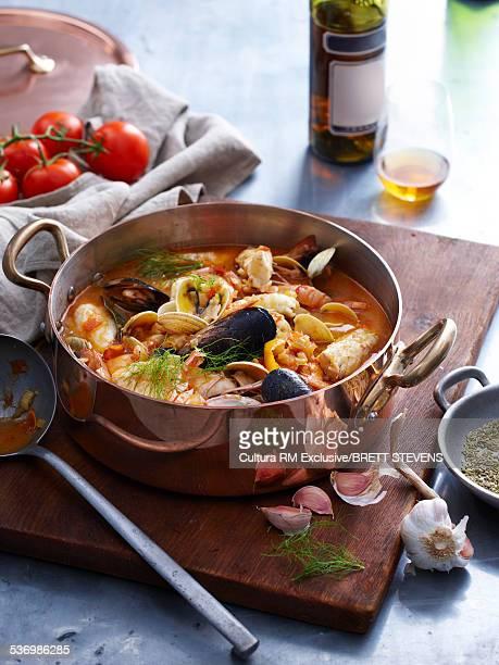 Pan of bouillabaisse, fish stew on chopping board
