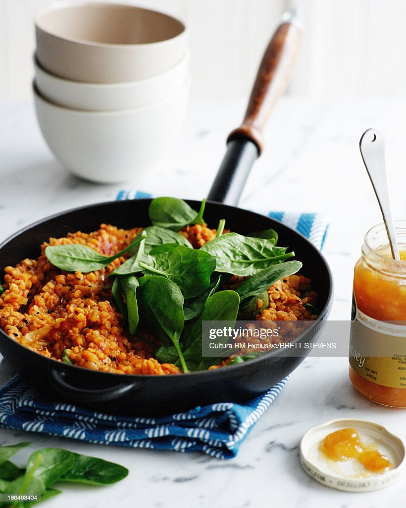 Pan of spiced dahl with jar of mango chutney : Stock Photo