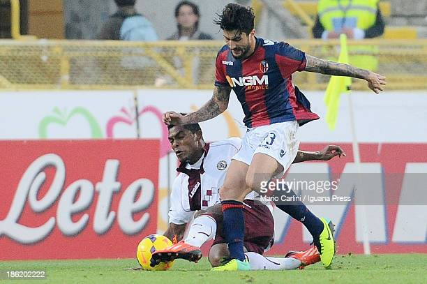 Panagiotis Kone of Bologna FC competes the ball with Ibrahima Mbaye of AS Livorno Calcio during the Serie A match between Bologna FC and AS Livorno...